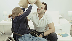 Photo of Long-term Care male Caregiver with child in wheelchair
